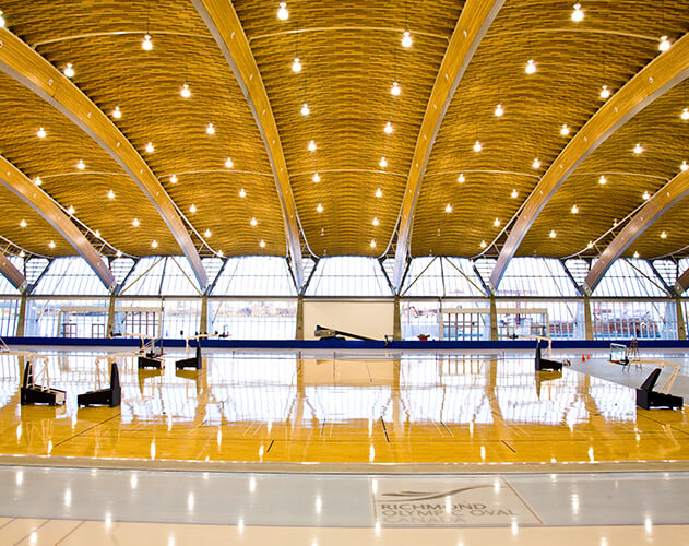 "Interior of Richmond Olympic Oval<abbr>Richmond, B.C. Canada<br>2 ""x 4"" SPF commodity dimension lumber and Douglas fir plywood (prefabricated WoodWave roof), Yellow cedar glulam posts</abbr>"